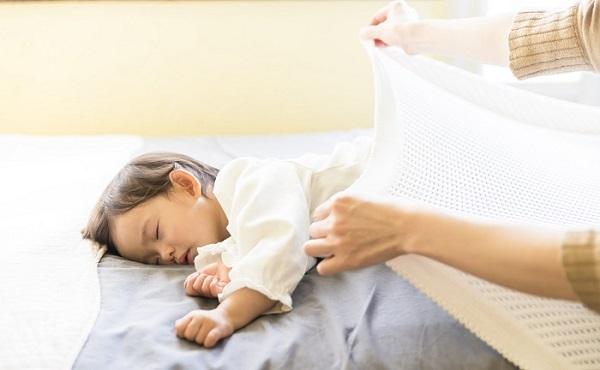 寝てしまった子どもにタオルケットをかけてあげる