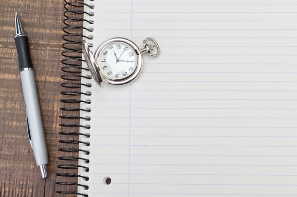 Antique pocket watch on notebook for notes. On textured wood.