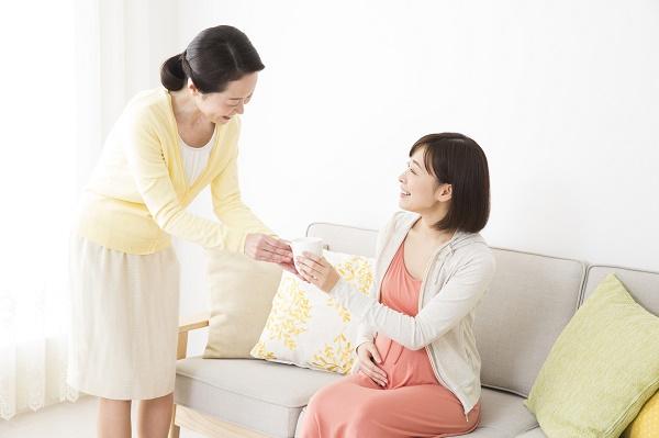 飲み物を飲む妊婦さんと母親