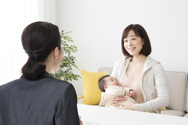 赤ちゃんを抱いて話す母親