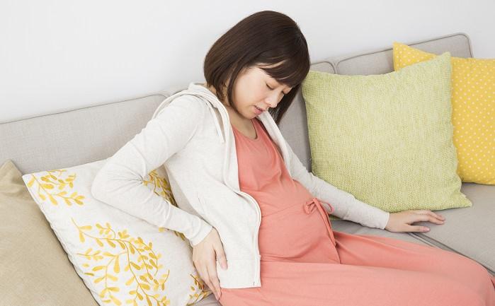 腰を手で押さえる妊婦