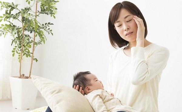 こめかみを押さえる母親と赤ちゃん