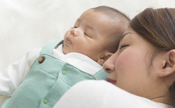 眠る赤ちゃんと母親