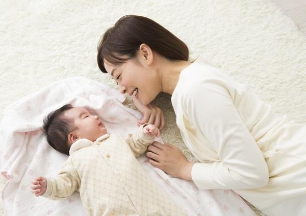 寝転がる赤ちゃんと母親
