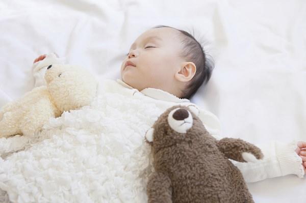 眠る赤ちゃんとぬいぐるみ