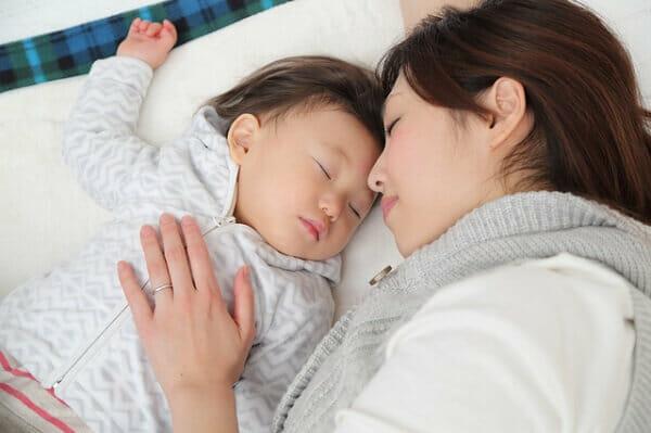 赤ちゃんと休息をとるママ